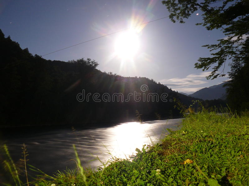 The moon by night on the background of the river stock image
