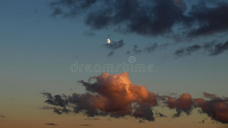 Moon in blue sky and red clouds stock image