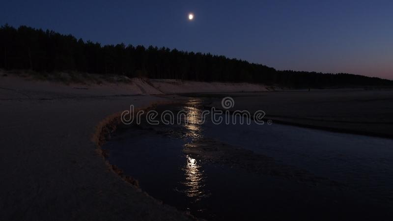 Moon in blue sky over sea and light reflection royalty free stock images