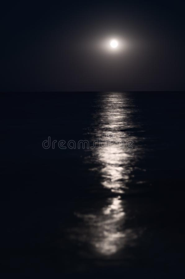 Moon in the night blue sky, sea horizon, waves, reflection of light. stock photo