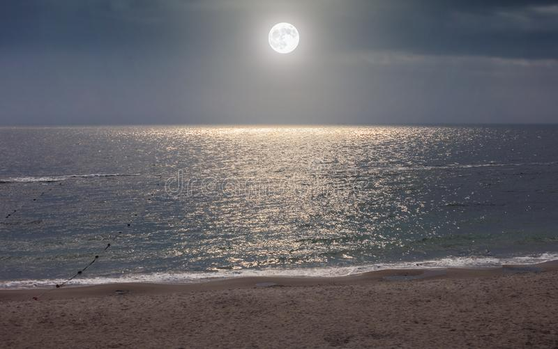 Moon in night sky over moonlight sea water. Travel background stock image