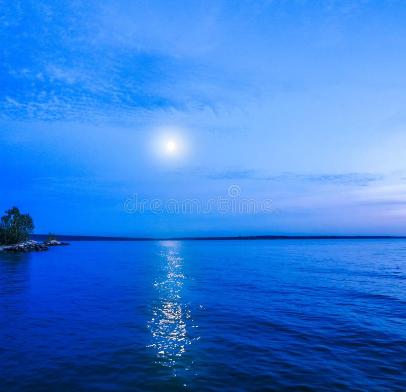 Moon in night sky over moonlit sea water. Travel background stock photo