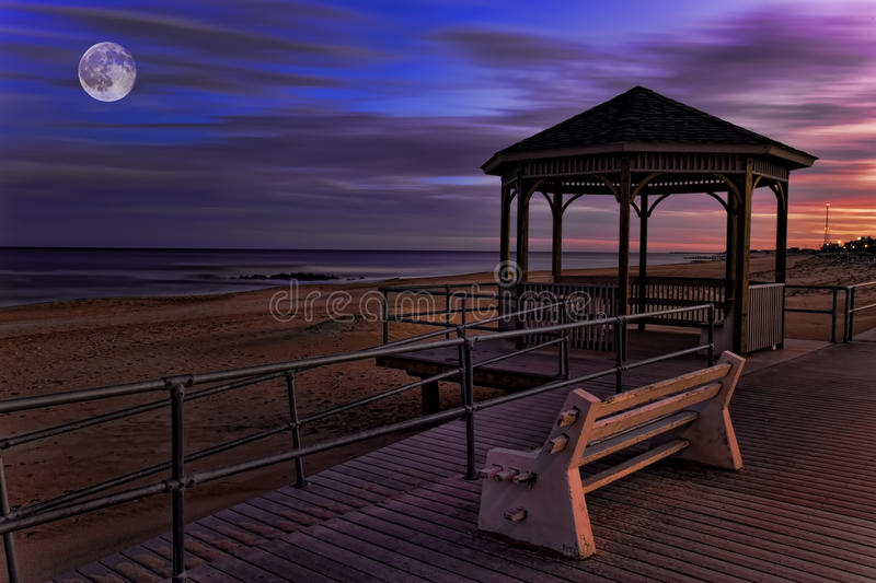 Moon over boardwalk by the sea. A Moon over boardwalk by the sea stock photos