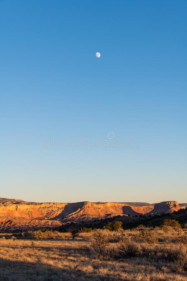 Moon over a colorful desert landscape at dusk over Ghost Ranch in New Mexico. Sunset and moon rising over the beautiful desert landscape at Ghost Ranch near stock photo