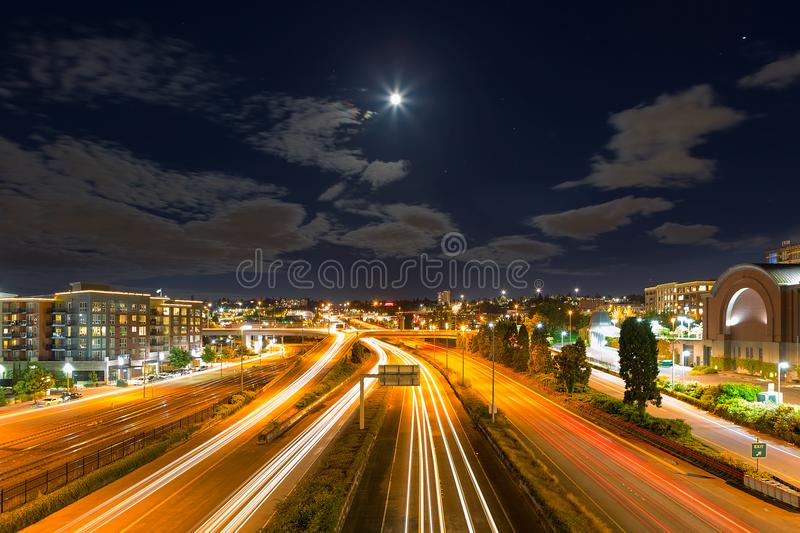 Moon over Freeway in Tacoma Washington. Moon Rise over freeway with long exposure light trails in Tacoma Washington at night stock photo