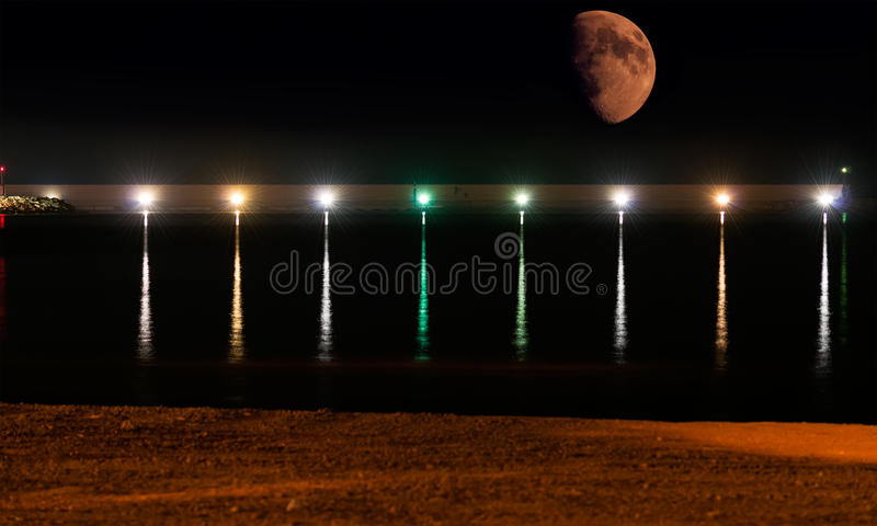 Moon over the harbor stock photography