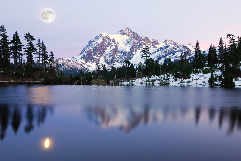 Moon Over Picture Lake. Picture Lake reflection of Mount Shuksan with snow royalty free stock photography