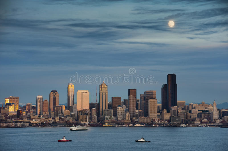 Moon over Seattle. A full moon rises above the Seattle, Washington skyline with tugs and ferries crossing Elliott Bay royalty free stock image