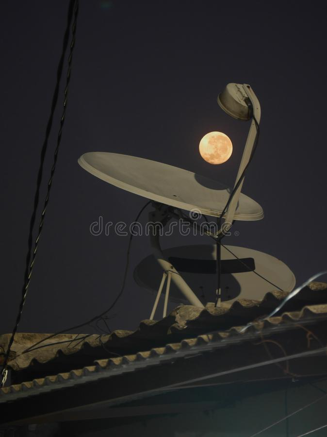 The moon and parabolic antenna that mounted on the roof. Photo of The Full moon and a parabolic antenna dish tha mounted on the roof royalty free stock images