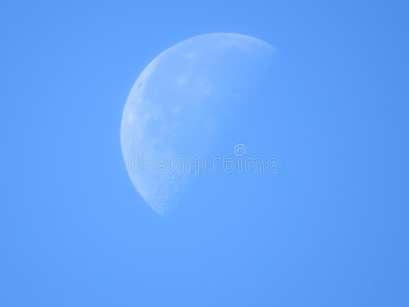 Moon in part shadow with blue sky background. royalty free stock photos
