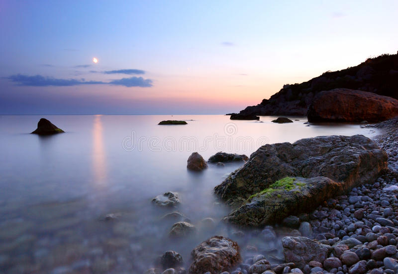 Moon path over the night sea after the sunset. Artistic view of the Moon path over the night sea with rocks and shore in the foreground and mountains in the stock photos