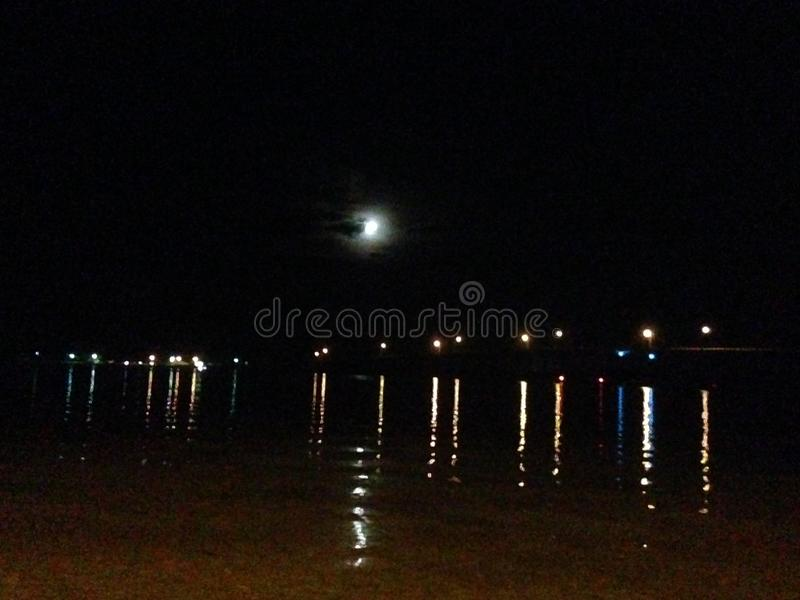 Moon peaking out from behind clouds reflecting over water stock photography