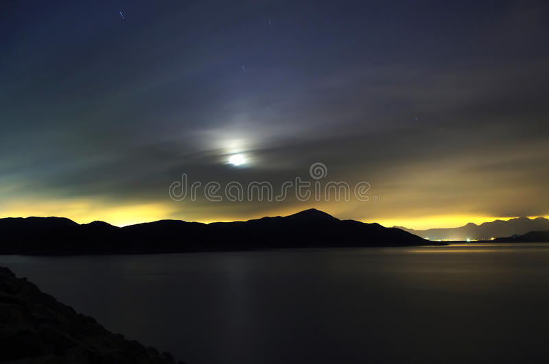 Moon and pond with amazing colorful lights. Moon and pond in a cloudy night, with the orange color at far from the city lights and the original dark blue colour royalty free stock photo