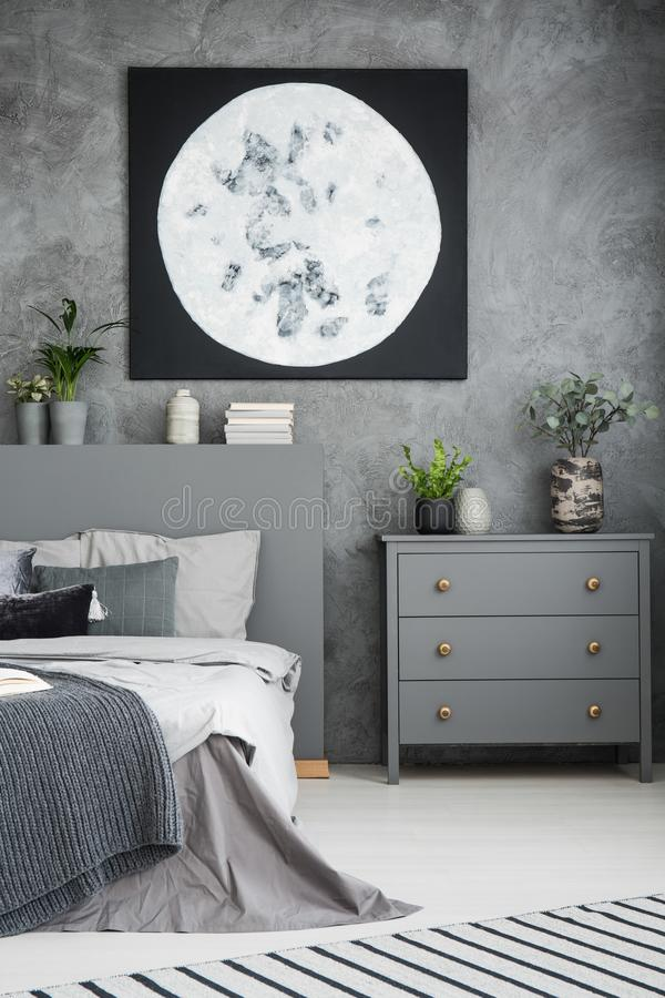 Moon poster above grey cabinet and bed in modern bedroom interior with plants. Real photo stock photography