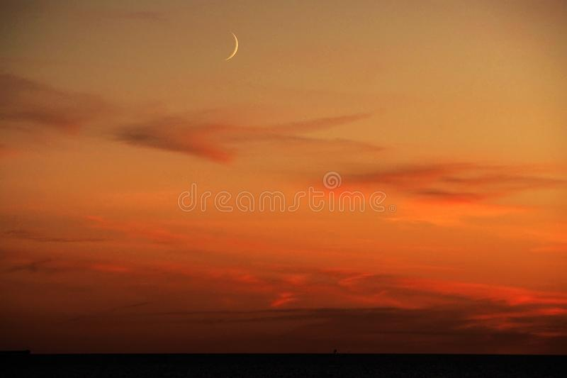 Moon and red clouds after sunset. Moon and red clouds, after sunset. over baltic sea in Latvia royalty free stock photography