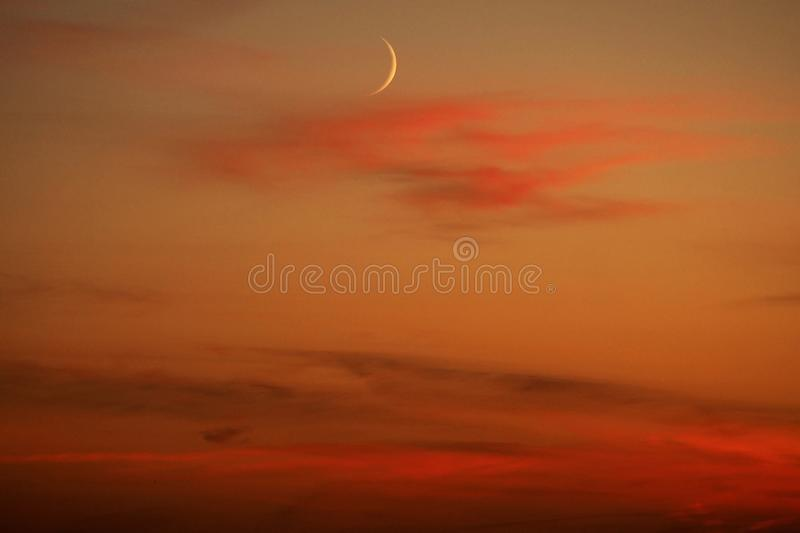 Moon and red clouds after sunset stock image