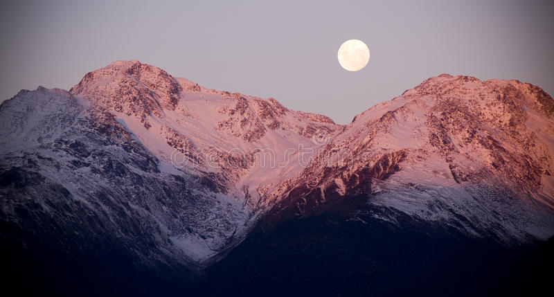 Moon Rise. Moon rising over two mountain peaks capped with snow and bathed in last rays of sunset royalty free stock photos