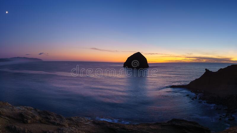 Moon rise and sunset over Cape Kiwanda. Along the Oregon Coast at Pacific City stock photo