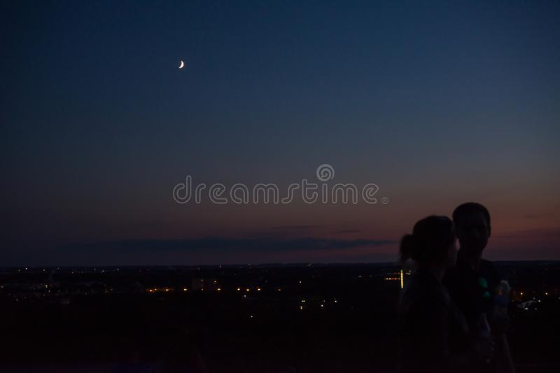 Moon rising over city lights royalty free stock photo