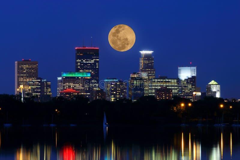 Moon Rises over Minneapolis Skyline. The full moon rises over the Minneapolis skyline with reflections of lights in Lake Calhoun royalty free stock photos