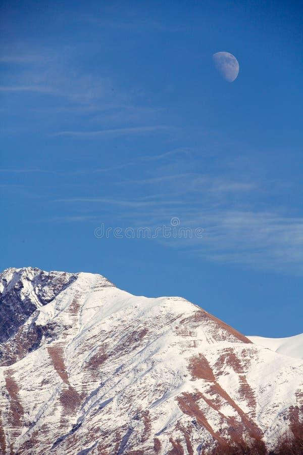 Moon rising over mountain stock photography