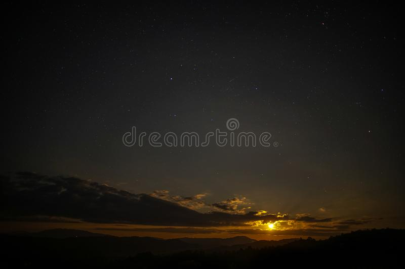 The moon is rising in the sky with stars. The moon is rising brightly in the sky with stars stock image