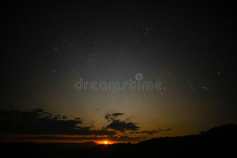 The moon is rising in the sky with stars. The moon is rising brightly in the sky with stars stock photo