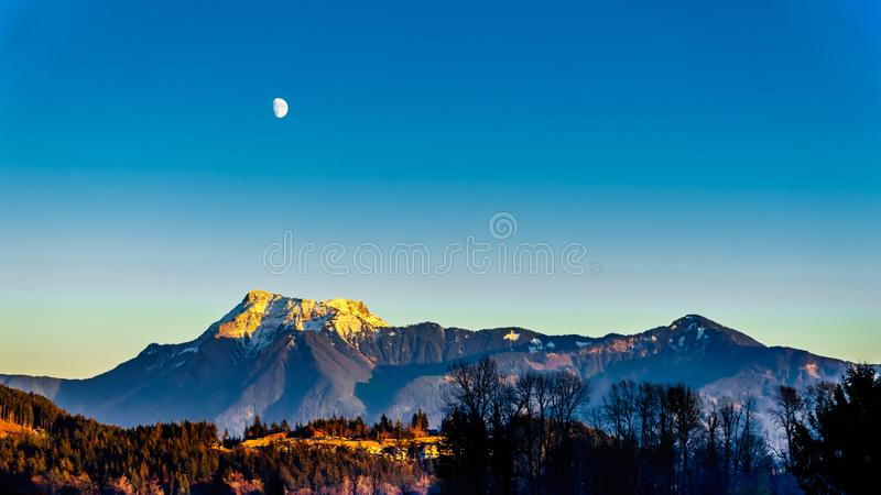 Cheam Mountain in the Fraser Valley of BC Canada. Moon rising at Sunset over Cheam Mountain in the Cascade Mountain Range. Viewed from the town of Harrison Mills royalty free stock photo
