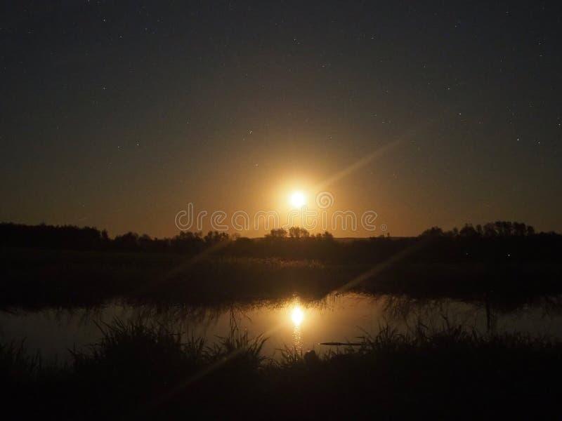 Moon rising under lake stock photography