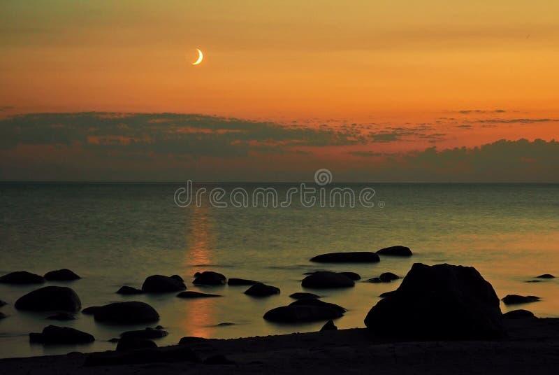 Moon set and orange sky over sea stone coast stock photography