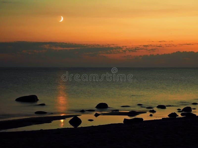 Moon set and orange sky over sea stone coast stock photo