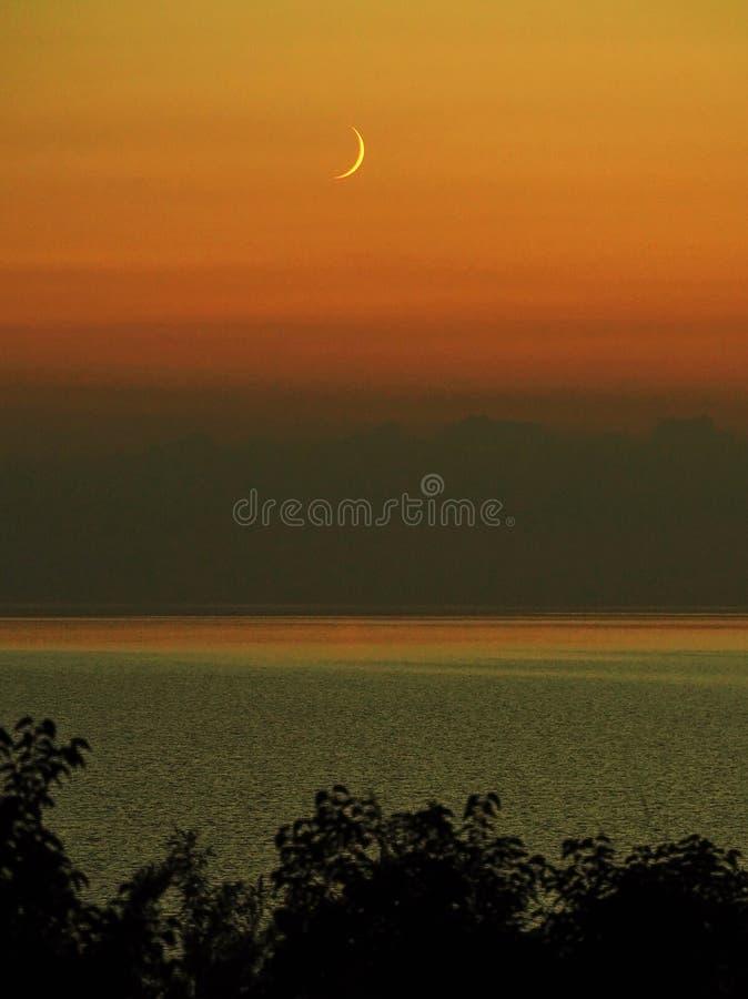 Moon set and orange sky after sunset stock photos
