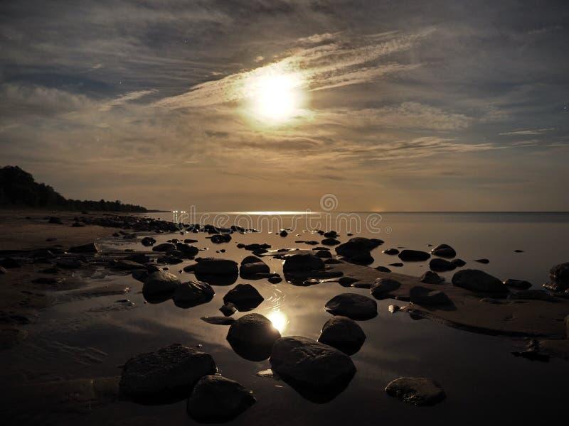 Moon set over Baltic sea stones coast stock image