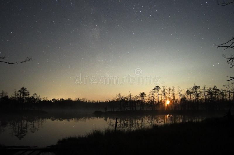 Moon set over forest lake and stars observing after sunset royalty free stock photography