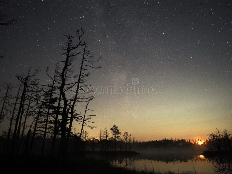 Moon set over forest lake and stars observing after sunset stock photo