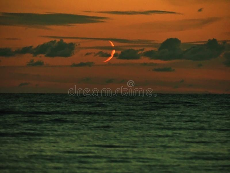 Moon set over sea observing and clouds after sunset stock photo