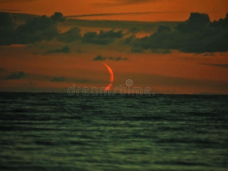 Red moon set over sea observing and clouds after sunset stock photos
