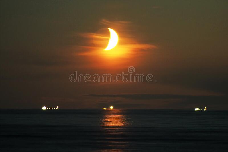 Moon set time and orange sky observing stock photos