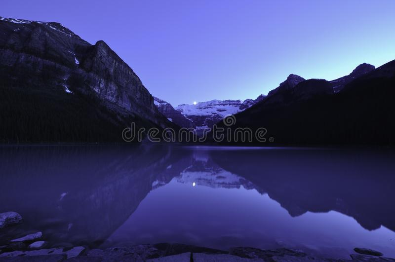 Moon setting over Lake Louise. With reflection of the mountains and the incredible blue evening light royalty free stock images