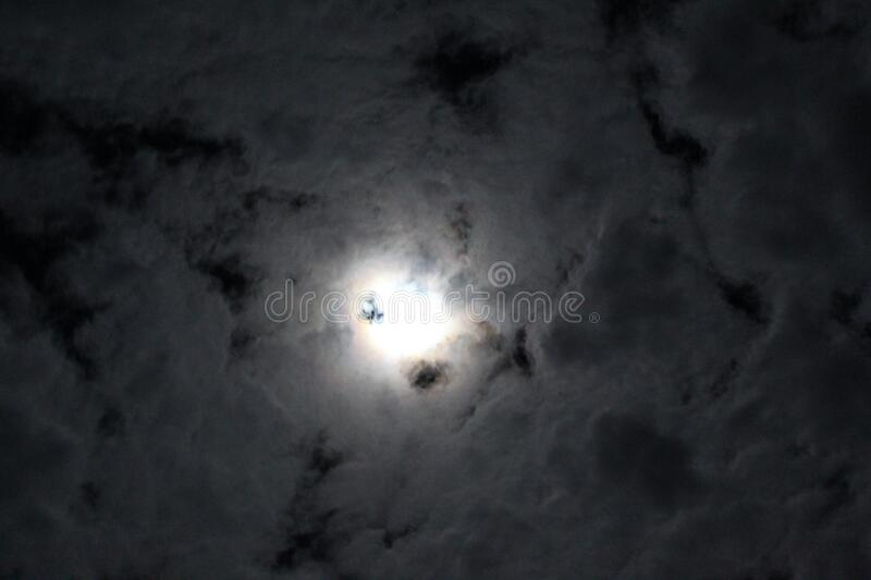 The moon shines in the clouds on a winter cold night. royalty free stock images
