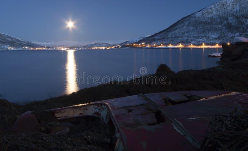 Moon shining on wrecked boat at arctic coastline stock photos