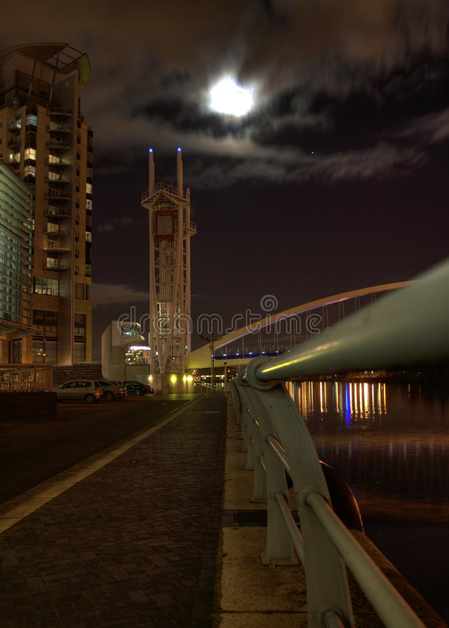 Moon Shock. Part of Salford Quays Suspension Bridge with full moon behind clouds and reflected lights on water stock photo