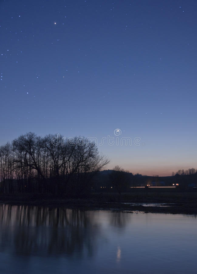 Moon and stars over river stock photography