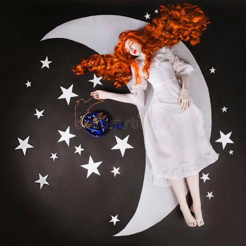 The moon and the stars. Young fairy woman with very long hair in white dress on black background. A beautiful girl with pale skin stock photo