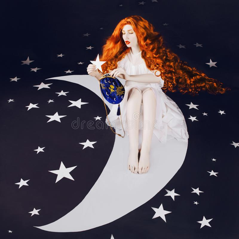 Moon and stars. Young fairy woman with very long hair in white dress on black background. A beautiful girl with pale skin. Renaissance fairy princess sit on royalty free stock photos
