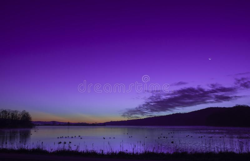 Moon at sunrise on a lake with reflections stock photo