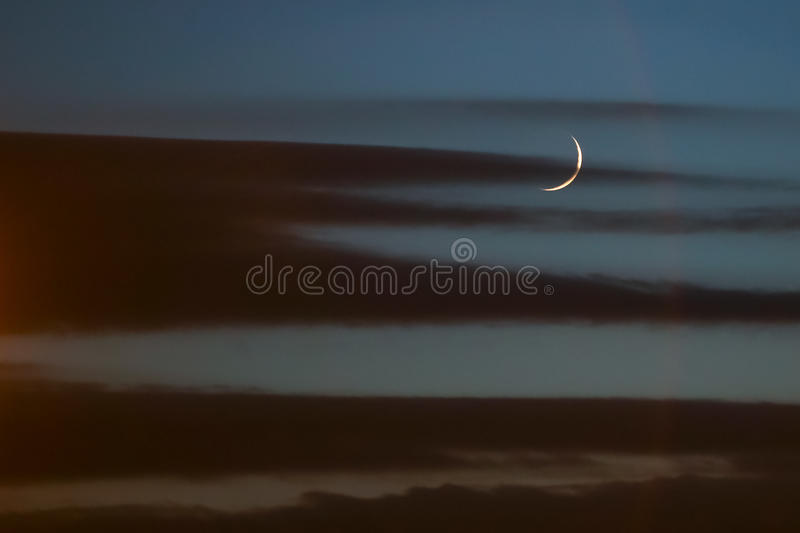 Moon at sunset. A moon breaking through the clouds at dark sunset royalty free stock images