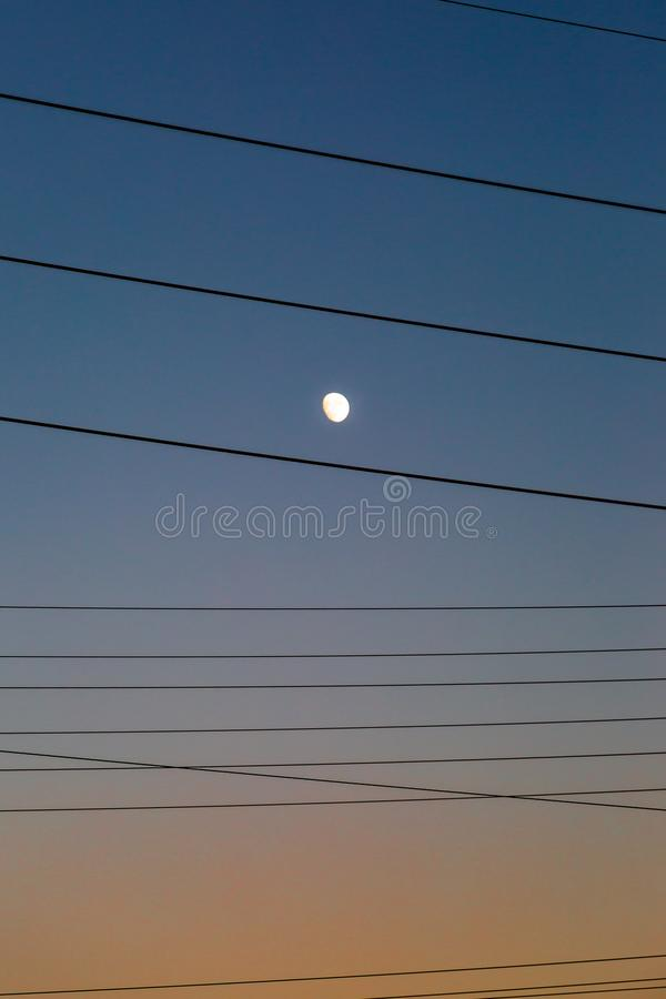 The Moon at Sunset. The Moon and Telephone Wires against a Sunset Sky stock photography