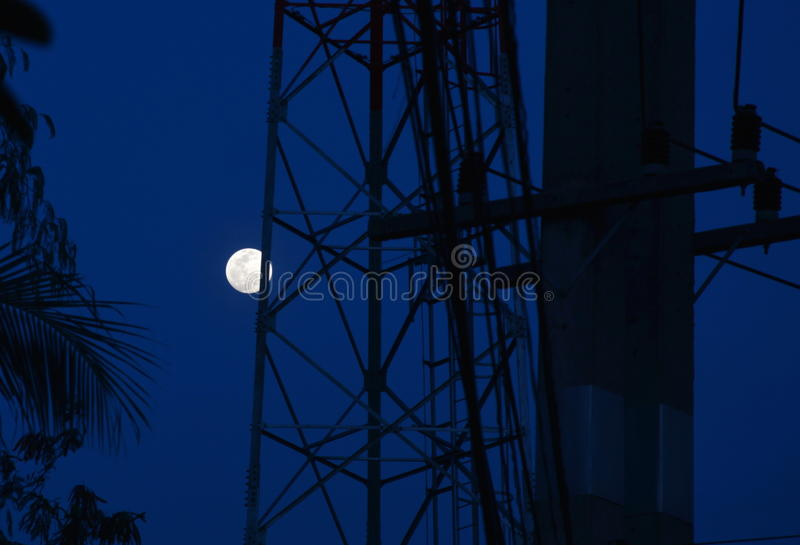 Moon under telecommunication tower. On early night stock photography