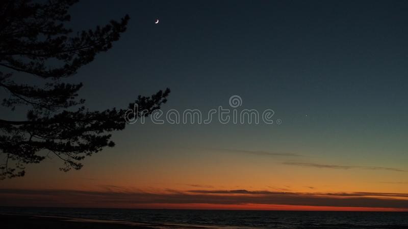 Moon and Venus observing after sunset. Moon, Venus and stars observing, on blue sky, after sunset, over sea stock photography